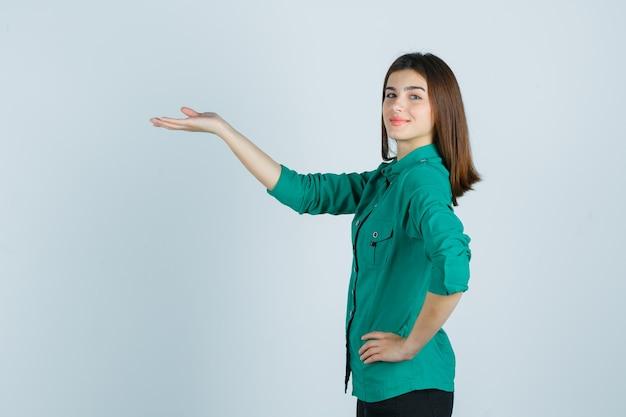 Bella giovane signora in camicia verde che finge di mostrare qualcosa e sembra allegra.