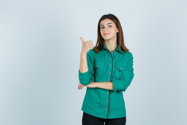 Bella giovane signora in camicia verde che mostra pollice in su e che sembra sicura, vista frontale.