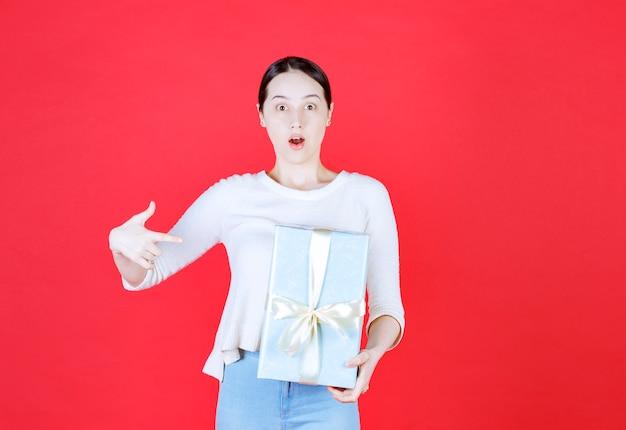 Bella giovane donna che tiene in mano una confezione regalo e punta il dito su di essa