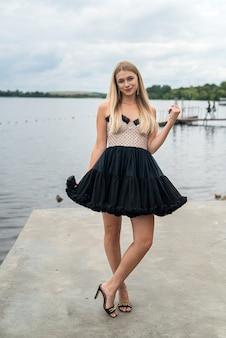 空と水、自由を背景に長く暗いドレスを着た美しい若い女性