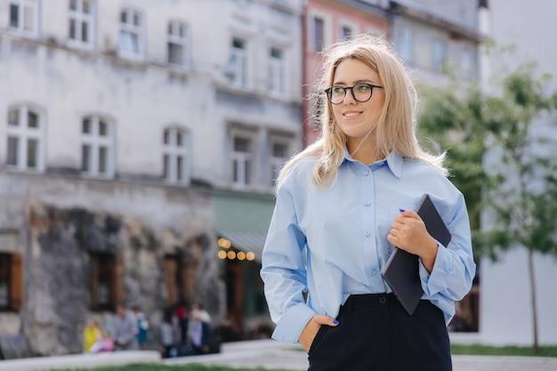 Красивая молодая дама в голубой рубашке, черных штанах и очках, держа цифровой планшет, стоя на улице. понятие о людях и современных технологиях.