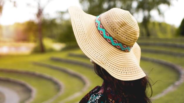 ドレスタッチ麦わら帽子を通して輝く美しい若い女性。稲作のように丘の中腹を歩く女の子