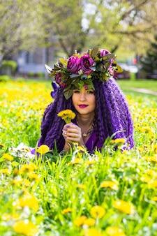 Красивая молодая леди, лежа в поле цветов