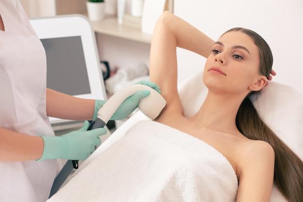 医療用ソファに横になり、脇の下を真空吸引してレーザー脱毛をしながら落ち着いて見える美しい若い女性