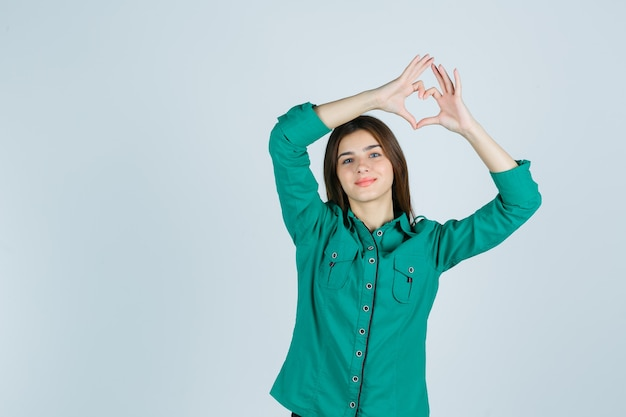 Beautiful young lady making heart gesture in green shirt and looking cheerful. front view.