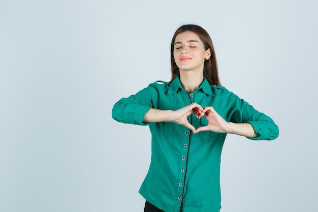 Bella giovane signora che fa il gesto del cuore in camicia verde e che sembra pacifica, vista frontale.
