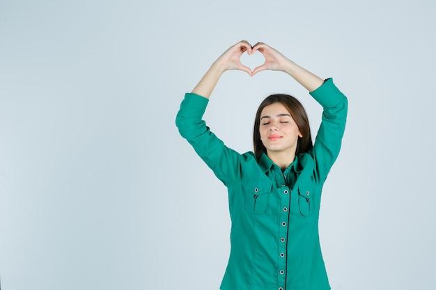緑のシャツを着て頭上でハートジェスチャーをし、リラックスして見える美しい若い女性。正面図。