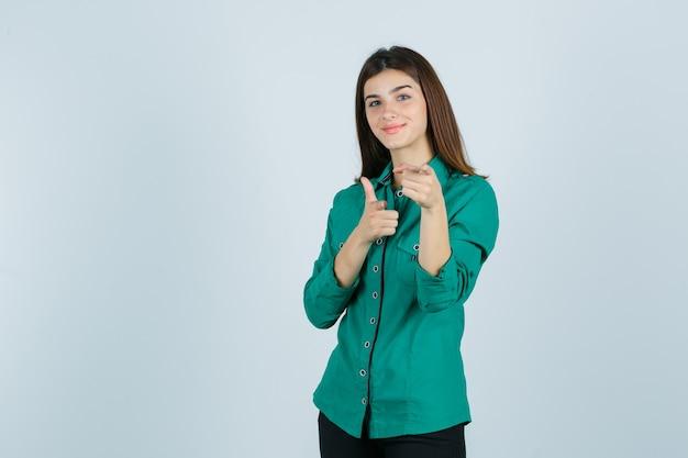 緑のシャツを着てカメラを指して、陽気に見える美しい若い女性、正面図。