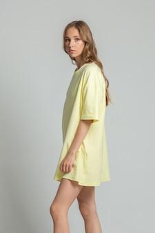 長い黄色のtシャツで横顔にポーズをとる美しい若い女性