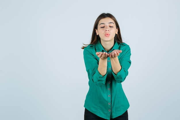 Bella giovane signora che invia un bacio d'aria con le labbra imbronciate in camicia verde e sembra pacifica, vista frontale.