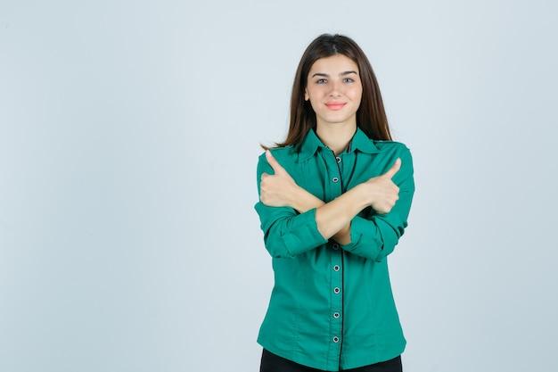 Bella giovane signora che mostra i doppi pollici in su in camicia verde e che sembra allegra, vista frontale.