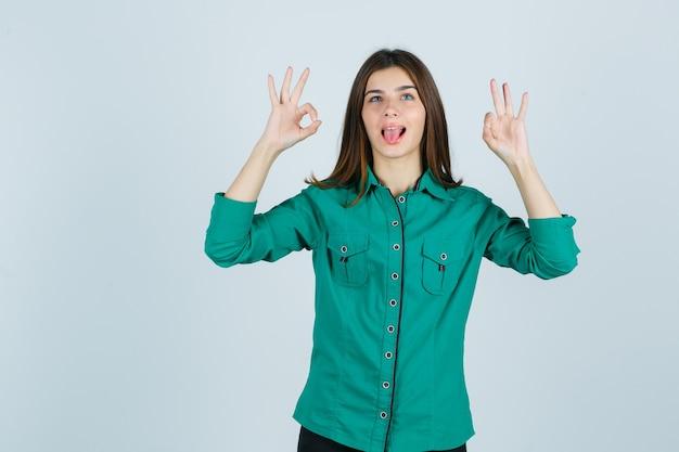 Bella giovane signora che mostra il gesto giusto mentre attacca fuori la lingua in camicia verde e sembra divertente, vista frontale.