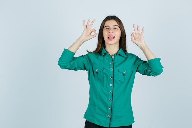 Bella giovane signora che mostra il gesto giusto mentre attacca fuori la lingua in camicia verde e sembra felice, vista frontale.