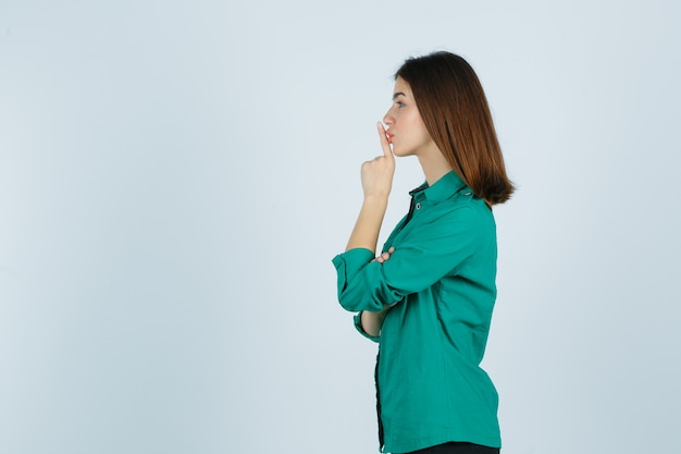 Beautiful young lady showing silence gesture in green shirt and looking careful. .