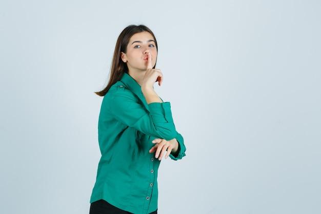 緑のシャツで沈黙のジェスチャーを示し、注意深く見ている美しい若い女性。正面図。