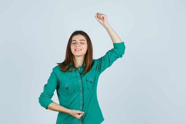 Красивая молодая дама показывает жест победителя в зеленой рубашке и выглядит блаженным. передний план.