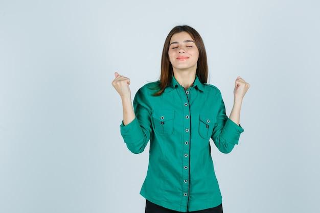 緑のシャツで勝者のジェスチャーを示し、幸運な正面図を見て美しい若い女性。