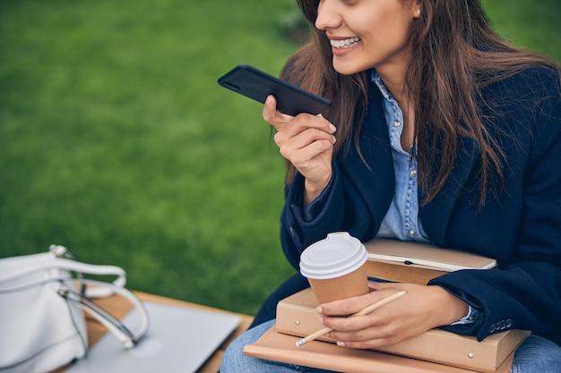 전화로 이야기하고 책과 함께 커피를 들고 밖에 앉아있는 동안 웃는 아름다운 젊은 아가씨