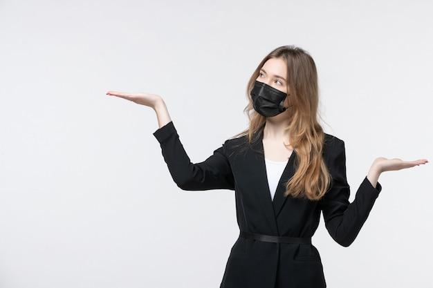 Bella giovane donna in tuta che indossa una maschera chirurgica e spiega qualcosa su bianco
