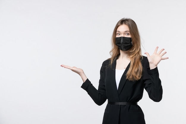 Bella giovane donna in tuta che indossa una maschera chirurgica e indica qualcosa che mostra cinque su bianco