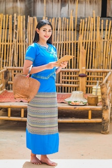 Beautiful young lady in a traditional thai dress with a tablet to receive customer orders.