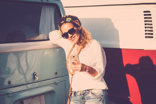 晴れた日に屋外で携帯電話のインターネット技術を使用している美しい若い女性-古いヴィンテージバスの青と赤-技術を使用して陽気な人々のための流行のコンセプト
