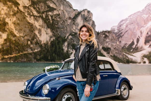 山の湖の前でポーズをとって革のジャケットの下にニットのセーターを着ている美しい若い女性