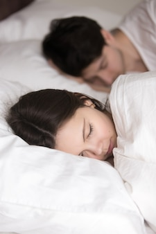 Beautiful young lady with beloved man sleeping in comfortable be