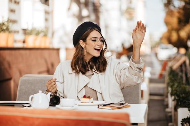 갈색 물결 모양의 헤어스타일, 붉은 입술, 세련된 안경, 베레모, 베이지색 트렌치 코트, 화창한 날 도시 카페 테라스에서 치즈케이크와 차를 마시며 누군가에게 인사하는 아름다운 젊은 여성