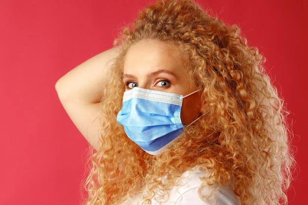医療用フェイスマスクを身に着けている巻き毛の美しい若い女性