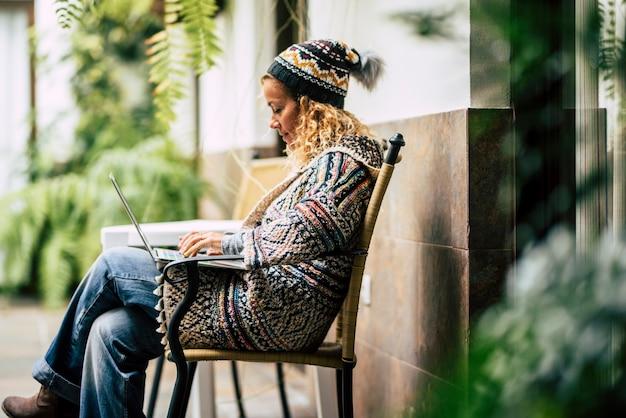 美しい若い女性は、周りの緑の植物とベンチに座って屋外のコンピューターのラップトップで動作します