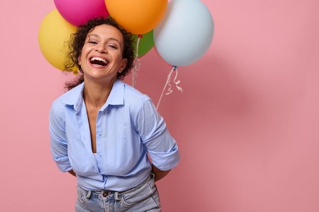 カメラを見て笑って、彼女の背中の後ろに風船を持って、広告のためのコピースペースとピンク色の背景で隔離の喜びと幸せな感情を持つ美しい若いラテンアメリカの女性