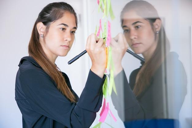 아름 다운 젊은 라틴 사업가 표시와 함께 스티커에 쓰기. 프로젝트에 대한 아이디어를 공유하고 메모를 작성하는 집중된 전문 여성 관리자