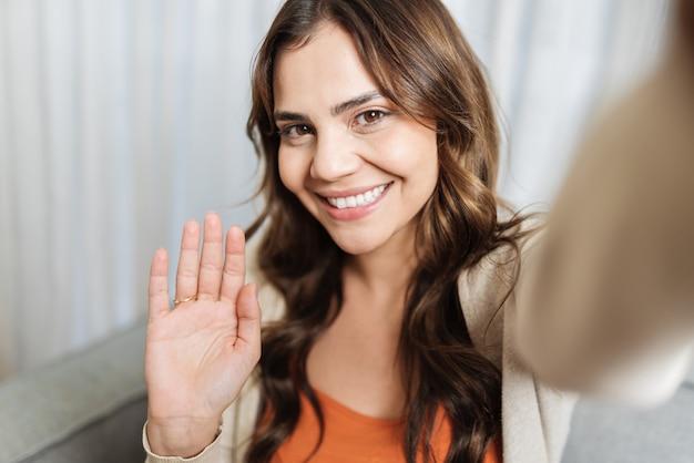 카메라나 전화를 손에 들고 웃고 있는 아름다운 라틴 여성과 영상 통화를 하거나 팬, 영상 통화 및 블로거 개념 pov를 위한 비디오를 녹화하고 있습니다.