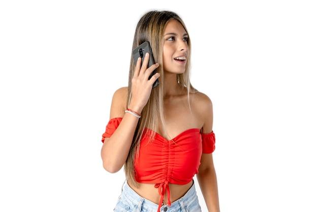 白い背景の上の彼女の携帯電話でメッセージを聞いている美しい若いラテン女性。
