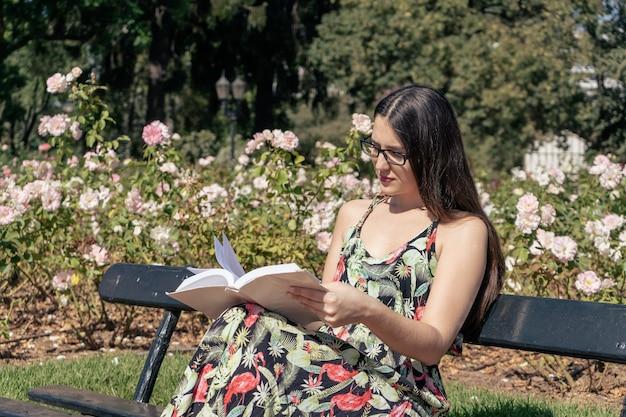 本を読んで集中している公園で黒い眼鏡と花のドレスを持つ美しい若いラテン女性。文化とレクリエーションの概念。
