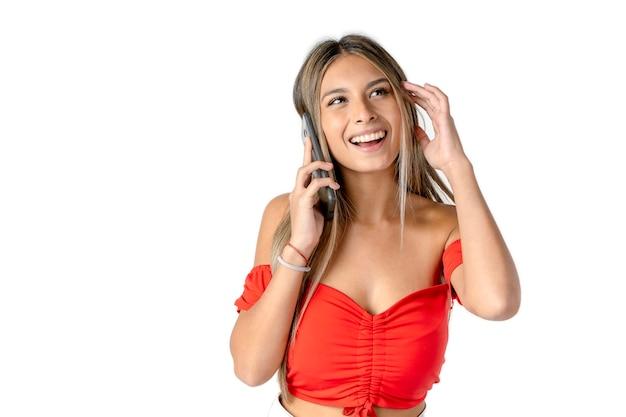 행복 한 표정과 흰색 배경 위에 그녀의 휴대 전화에 메시지를 듣고 있는 동안 머리에 손을 가진 아름 다운 젊은 라틴 여자.