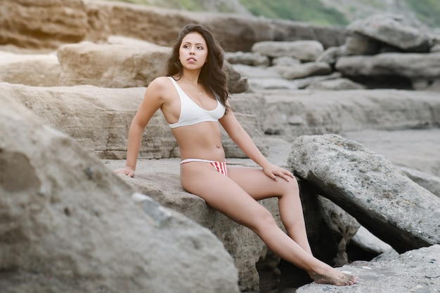Beautiful young latin woman with long black hair, happily sunbathing on some rocks at the beach