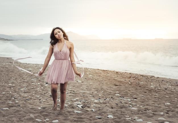長い黒髪の美しい若いラテン女性、夕暮れ時にビーチを走り、エレガントなピンクのドレスを着て、リボンを手に遊んで踊る