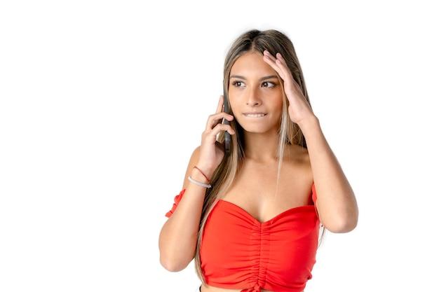 흰색 배경 위에 그녀의 휴대 전화에 메시지를 듣고 있는 동안 놀란 표정과 머리에 손을 가진 아름 다운 젊은 라틴 여자.
