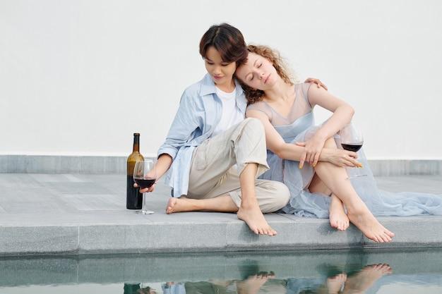 スイミングプールのそばに座って赤ワインを飲む美しい若いレズビアンのカップル