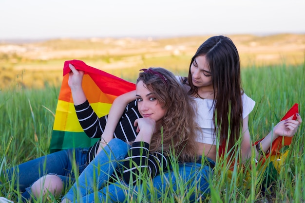 Beautiful young lesbian couple with the rainbow flag, equal rights for the lgbt community
