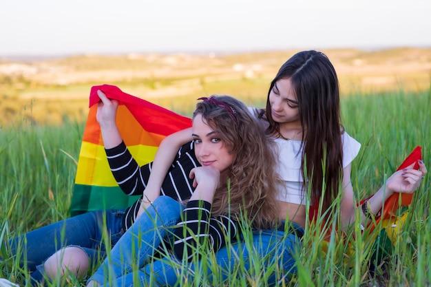 虹色の旗を持つ美しい若いレズビアンのカップル、lgbtコミュニティの平等の権利