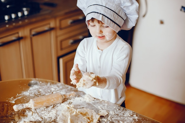 A beautiful young little daughter is cooking in the kitchen at home
