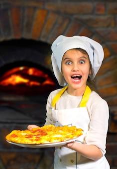 진짜 이탈리아 돌 난로에서 피자를 준비하는 아름 다운 어린 소녀