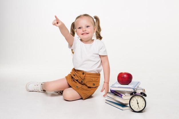 Bella giovane bambina seduta sul pavimento libri