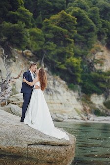Beautiful young long-haired bride in white dress with her young husband near river
