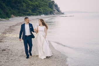 Beautiful young long-haired bride in white dress with her young husband on the beach
