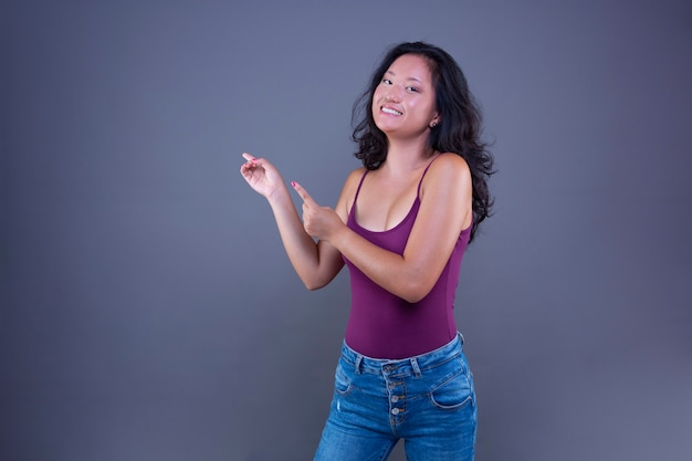 Beautiful young long-haired brunette chinese woman extending her hand to the side to show or indicate something.