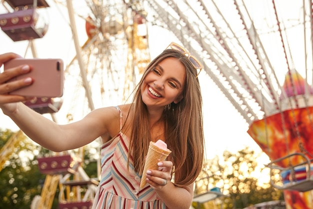 ロマンチックな夏のドレスを着た美しい若い長い髪のブルネットの女性は、彼女の携帯電話で自分撮りをしながら、アイスクリームコーンを手に保ち、元気に笑っている間、アトラクションの上でポーズをとる